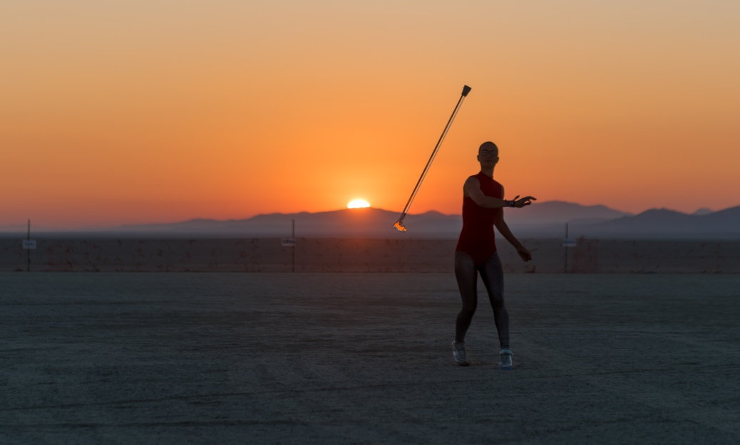 In the background is a desert horizon with a sunset. In the foreground is a silhoetted person throwing a clear cane towards the camera.