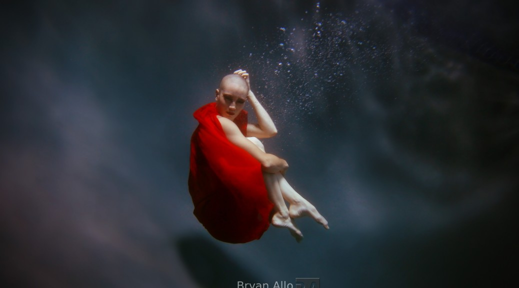 A picture from the side of a light-skinned bald person holding knees to chest in dark water, with red fabric surrounding their body, leaving their head, arms, and lower legs bare.
