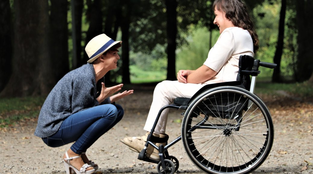 Two light-skinned people outside in nature. On the left is a person squatting on their heels, wearing heels, gesturing animatedly as they look up to a person who is laughing at what they're saying. The person on the right is in a wheelchair.