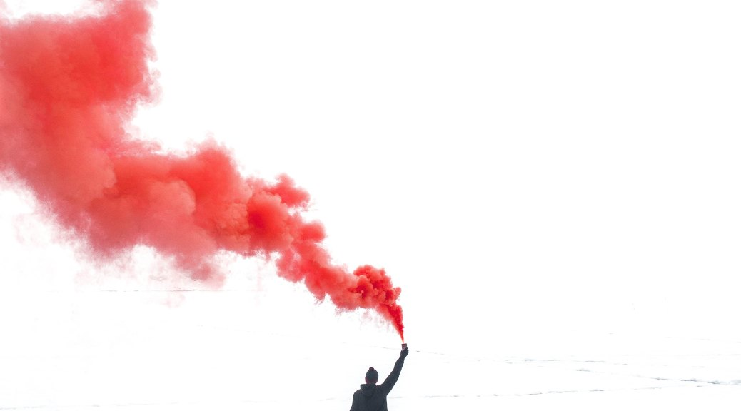 a silhouetted person stands on barren land holding a flare in the air. The image is black and white except for the flare, which is a string of cloudy red smoke drifting up and behind the person.