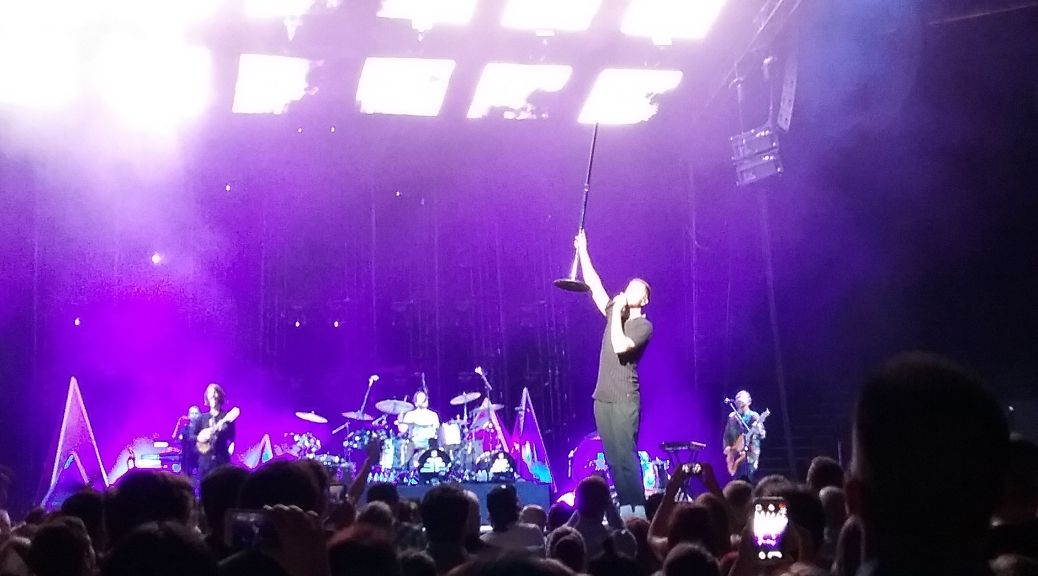Dan Reynolds on stage holding a mic stand in the air. The rest of the band is visible in a purple haze