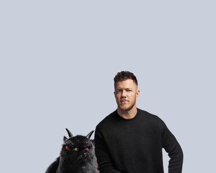 Dan Reynolds sits in front of a plan background with a black shirt on, looking at the camera. Next to him is a black beast with red eyes and two horns.