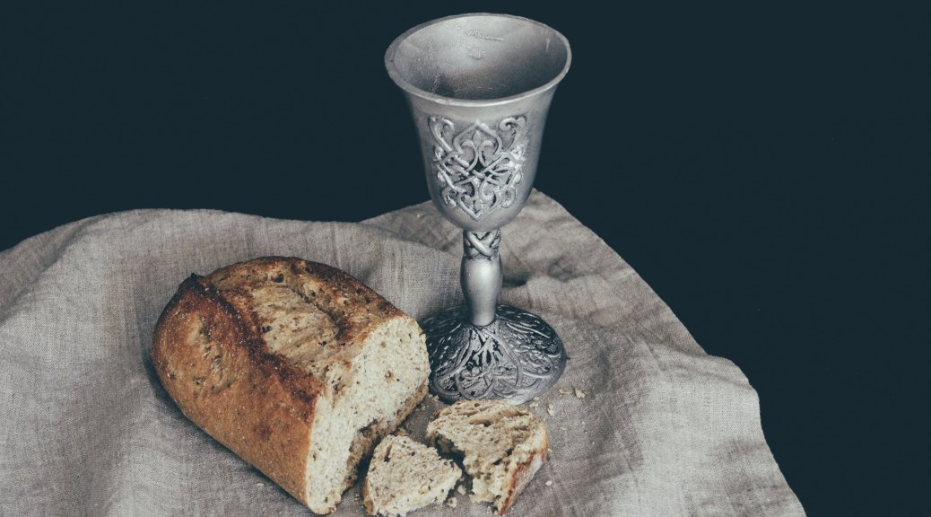 A chalice and half-loaf of bread resting on tan fabric with a black background