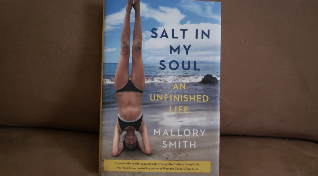 A hardback copy of Salt in My Soul is propped up on a brown couch cushion