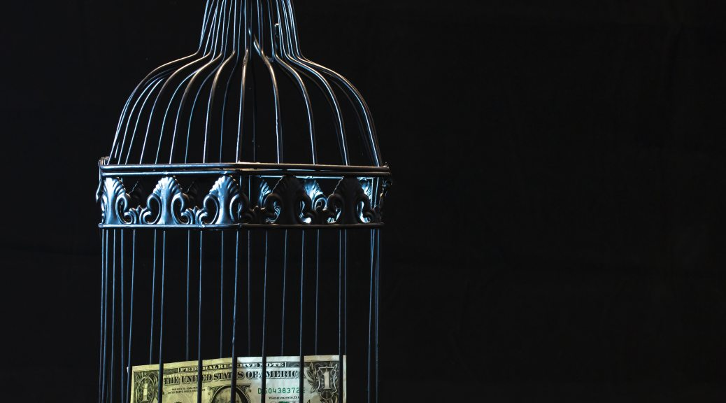 A picture of a small black metal birdcage containing a dollar bill. The image is dark, with blackness surrounding the featured image