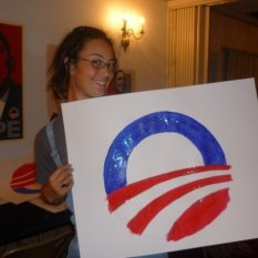 "A picture from 2008 of a white-appearing person holding a poster with half of a blue ""O"" rising like the sun over a horizon depicted by three red stripes. The whole image forms a circle with a lot of negative space"