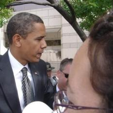 A picture of Barack Obama in 2008 with his head turned sideways. In the front of the frame, a white-appearing forehead and part of someone's glasses are visible