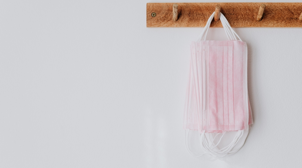 A picture of pink medical disposable face masks hanging on wood hooks on a white wall