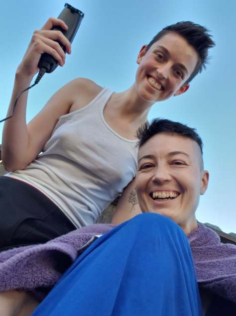 A selfie of two white-appearing queers as one of them cuts the other one's hair to match their own