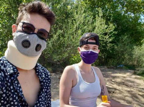 A selfie of two white-appearing queers on a beach. They are social distancing and wearing masks. One has a baseball hat on backwards and the other wears a tan fabric neck brace
