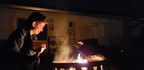 A dark photo of a white-appearing person looking over a back yard fire as its light shines on their face