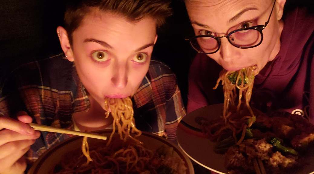 A selfie of two white-appearing people eating Chinese food with noodles hanging out of their mouths as they make a funny face at the camera with big eyes