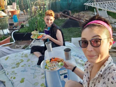 A selfie of two white-appearing people socially distanced in a back yard on a picnic blanket holding plates of food