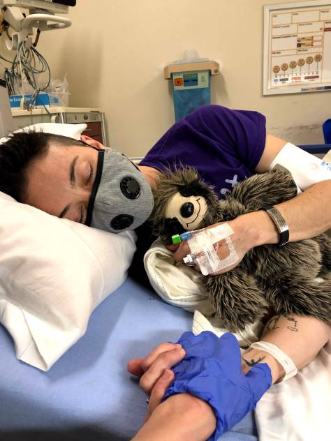 A picture of Charis, a white-appearing queer person wearing face mask and holding a stuffed sloth as they lie in a hospital bed sideways with eyes closed. Their other hand holds the gloved hand of the photographer, not visible in the frame.