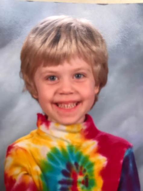 A white child with medium length blonde hair and a tie-dyed turtleneck shirt smiling in what appears to be a school portrait