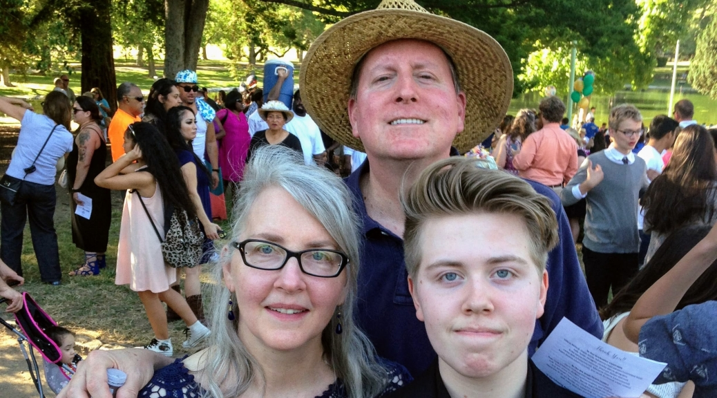 A family photo outside with a white mother, father, and son at his graduation from middle school. He wears a black robe. They all are smiling.