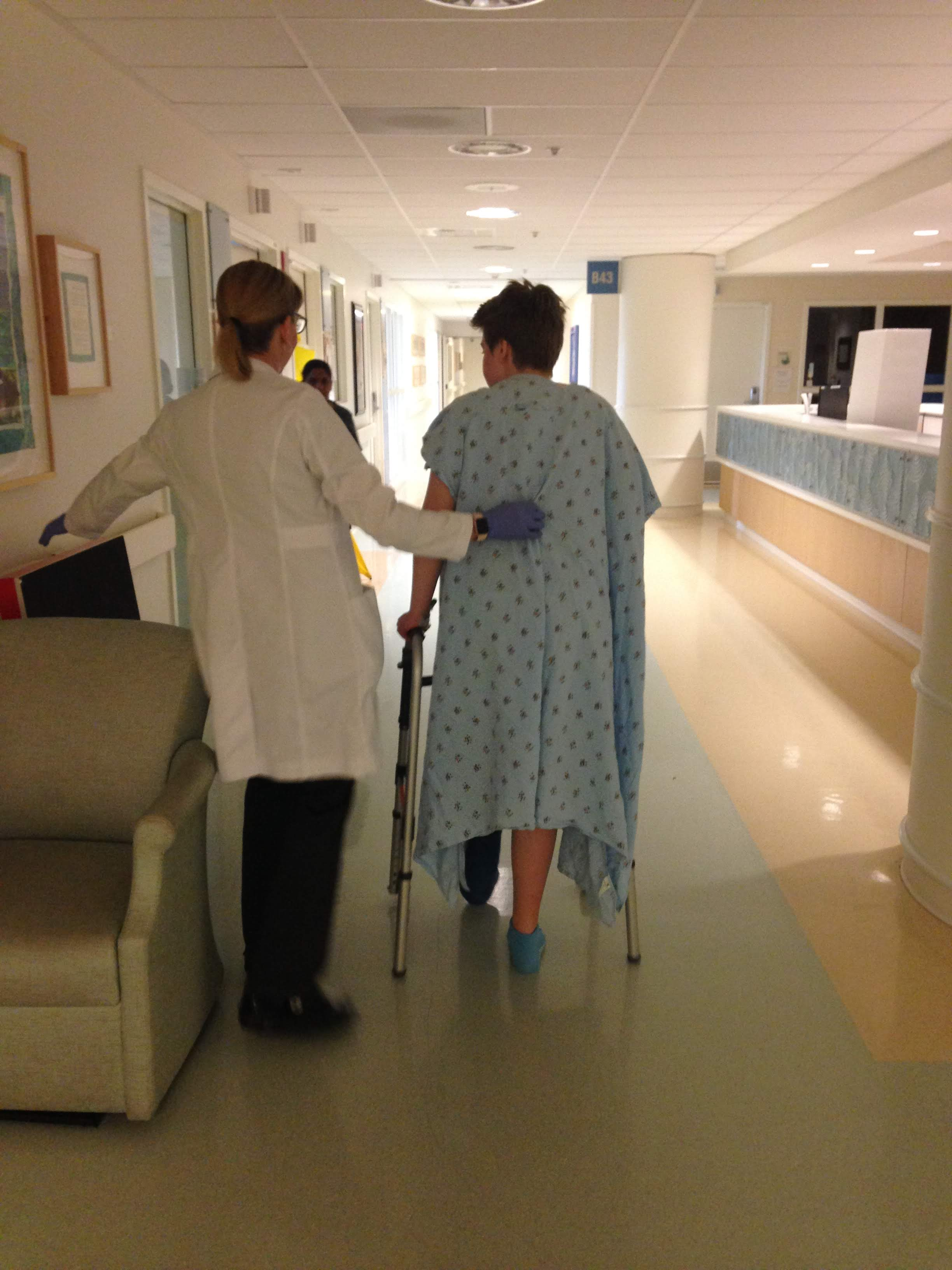 A picture from behind of a white-appearing healthcare provider with white lab coat with her hand slightly on the back of a young white teenager's back. He wears a blue hospital gown and takes a walk using a walker down a hospital hallway
