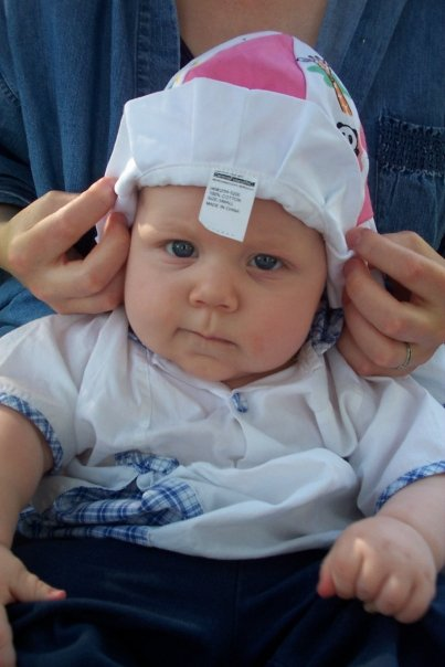 A white baby in an unseen lap. Adult hands are adjusting a hat on the baby's head as the baby looks at the camera